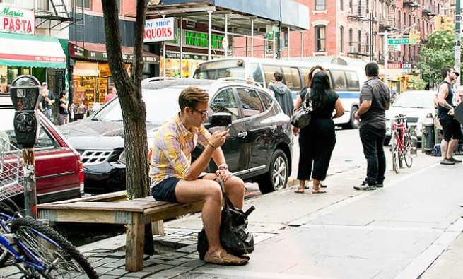 Man sitting on a city bench on his phone.