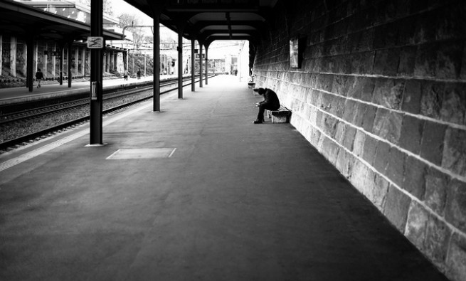 Black and white photo of a man waiting for a train