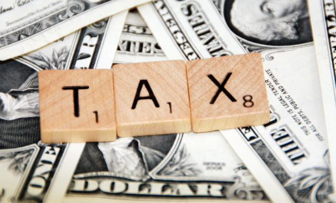 """Scrabble letters spelling out """"tax"""" over dollar bills"""