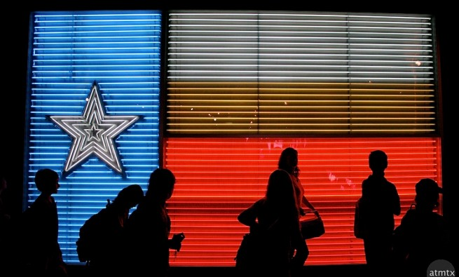 People in front of neon Texas flag