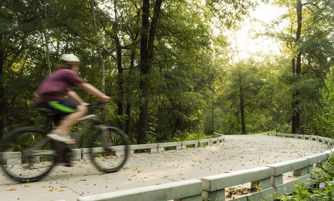 A cyclist rides the Halls Bayou Greenway trail, part of the Bayou Greenways 2020 initiative.