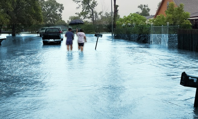 man and woman walk down a flooded street in Northeast Houston after Hurricane Harvey