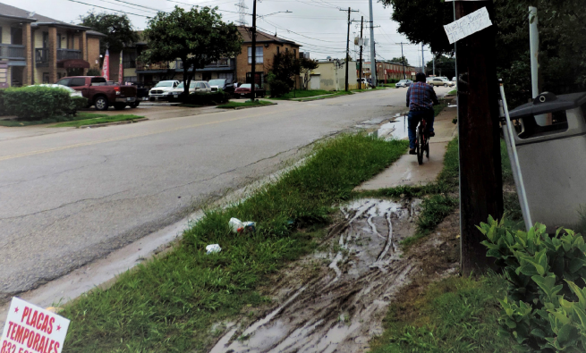 A muddy patch of grass interrupts the sidewalk in Gulfton as a bicyclist navigates onward