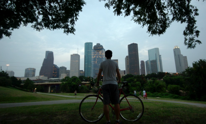 Man holding his bike in front of Houston skyline