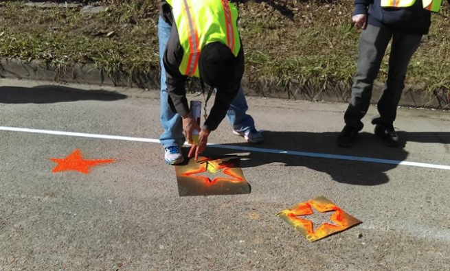 Men spray painting stars on a road
