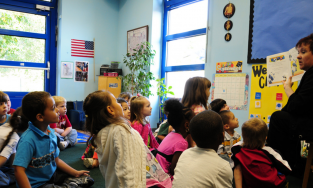 Classroom of students listening to a teach read a book
