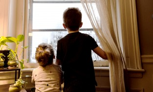 kids stand at window looking out