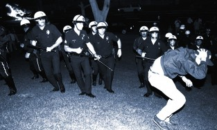 LAPD officers confront a protestor on the south lawn of City Hall while a police car burns during night one of the Rodney King Riots on April 29, 1992, in Los Angeles, California..