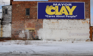 Image of election sign on brick wall for Mayor Clay in Indiana