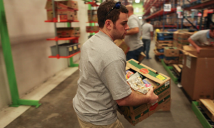 Image of a volunteer carrying a box of food