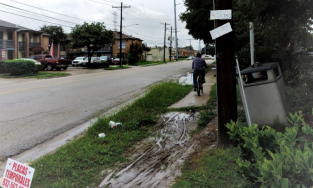 Man riding bike along rough, muddy sidewalk
