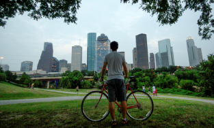 Man with his bike looking at the Houston skyline