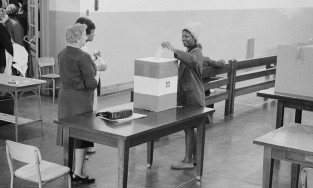 Photograph showing a young African American woman casting her ballot.